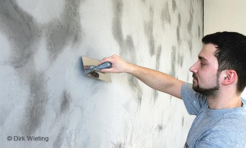 Mitarbeiter beim Spachteln einer Wand.