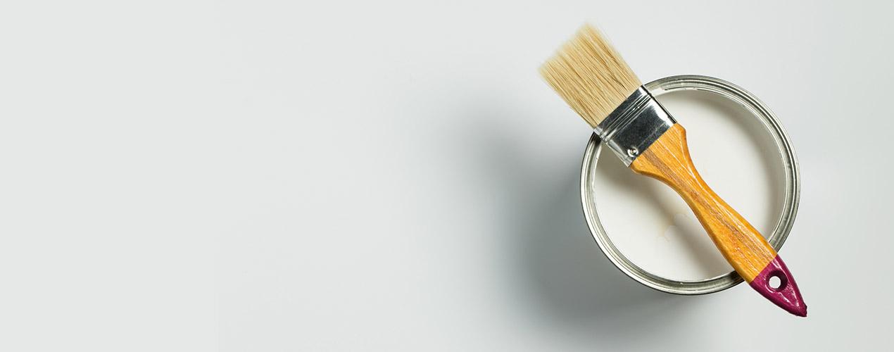 Ein Pinsel auf einer Dose die sich auf einem weißen Grund steht.
